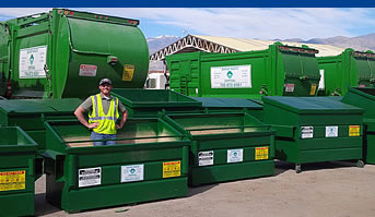 man standing in green dumpster
